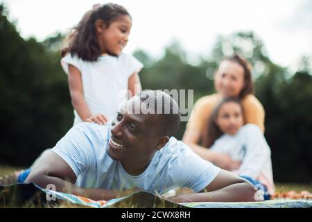 Happy man enjoying picnic in park with family