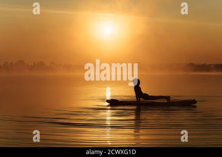 Silhouette of young man stretching body on sup board - Stock Photo