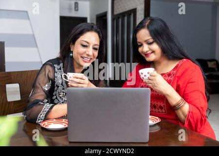 Two female friends sitting at home with laptop infront of them, holding tea cups and talking to each other. - Stock Photo