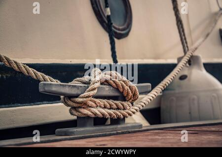 Close up of the mooring cleat with a boat rope tied around it. Connection visual concept as boat tied and linked to the pontoon.