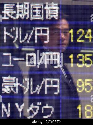 A pedestrian is reflected in an electronic board showing exchange rates between (from 2nd row to 4th row) the Japanese yen against the U.S. dollar, the euro, and Australian dollar, and market indices of Dow Jones, dollar outside a brokerage in Tokyo, Japan, May 28, 2015. The dollar hit its highest since December 2002 against the yen on Thursday due to expectations that U.S. interest rates will rise later this year, while the Australian dollar struck a six-week low following disappointing capital expenditure data. REUTERS/Yuya Shino - Stock Photo