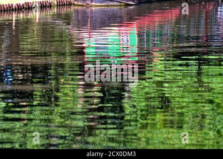 Abstract shapes created by the reflections of brightly painted narrow boat in water