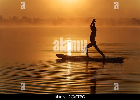 Silhouette of sportive man doing yoga on paddle board - Stock Photo