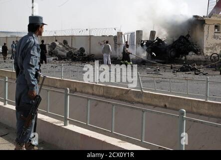 An Afghan policeman (L) watches as firefighters work at the site after a car bomb explosion in Lashkar Gah, capital of Helmand province July 31, 2011. The explosion killed at least six Afghan police in the southern city of Lashkar Gah on Sunday, said a spokesman for the Helmand provincial governor.  REUTERS/Abdul Malik Watanyar (AFGHANISTAN - Tags: CIVIL UNREST IMAGES OF THE DAY) - Stock Photo