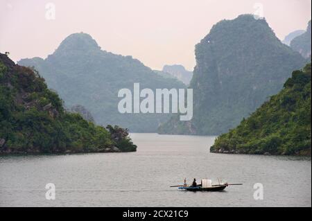 Vietnamese man in small fishing boat, Halong Bay, Vietnam - Stock Photo