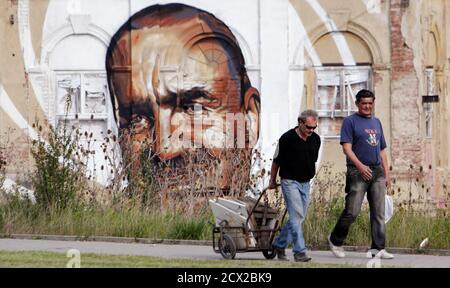 A man pulls a cart filled with pieces of scrap materials for recycling past a pre-election mural, depicting TOP09 political party chairman Karel Schwarzenberg, painted on an abandoned building in Prague October 8, 2013. The Czech Republic will hold an early election on October 25 and 26. REUTERS/David W Cerny (CZECH REPUBLIC - Tags: POLITICS ELECTIONS) - Stock Photo