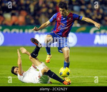 Levante's Xavi Venta controls the ball over Sevilla's Manu del Moral (on ground) during their Spanish first division soccer match at the Ciudad de Valencia Stadium in Valencia December 10, 2011. REUTERS/Heino Kalis (SPAIN - Tags: SPORT SOCCER)