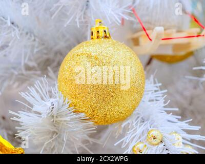 A golden ball hangs on the white branches of an artificial Christmas tree. Full screen photo - Stock Photo