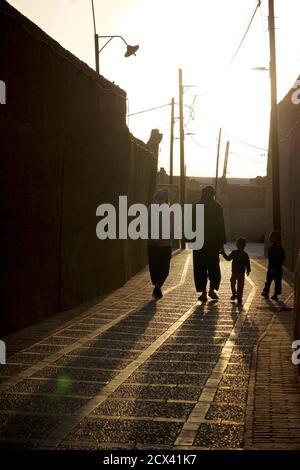 Iranian men and children walking through the alleyways of Yazd, Iran at sunset. - Stock Photo