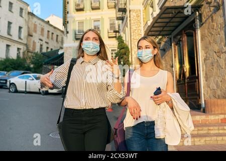 Two young business women in protective medical masks walking together Stock Photo