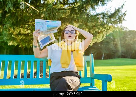 Symptoms of menopause in mature woman, female waves newspaper to cool off