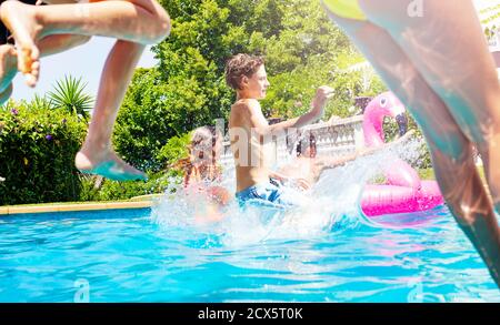 Boy in a group of friends jump into water pool together splashing down - Stock Photo