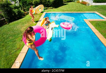 Group little kids in mid air jump into the swimming pool holding inflatable toys diving in the water - Stock Photo