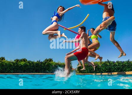 Group of happy teenage kids dive in the swimming pool water throw inflatable toys lifting hands have fun - Stock Photo