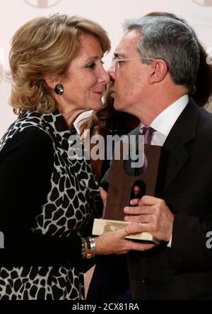 Former Colombian President Alvaro Uribe leans to kiss Madrid's regional president Esperanza Aguirre after  receiving 'La puerta del recuerdo' (The Memory Gate award in Madrid October 27, 2010.  REUTERS/Juan Medina  (SPAIN - Tags: POLITICS)
