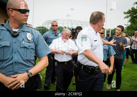 A police officer tells a journalist that he cannot ask any more questions as Ferguson Police Chief Thomas Jackson (C) walks away from a media availability regarding his office's handling of the release of information following the shooting of Michael Brown in Ferguson, Missouri August 15, 2014. REUTERS/Lucas Jackson (UNITED STATES - Tags: CIVIL UNREST CRIME LAW POLITICS)