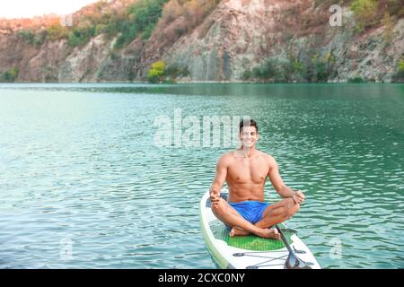 Young man practicing yoga on paddle board in river - Stock Photo