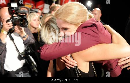 Social Democrat leader Helle Thorning-Schmidt is embraced by a supporter after claiming victory in a parliamentary election at the party's election headquarters in Copenhagen September 16, 2011. Thorning-Schmidt is set to become Denmark's first female prime minister, having persuaded voters she fix can the economy to win a close election race and end 10 years of centre-right rule. REUTERS/Fabian Bimmer (DENMARK - Tags: POLITICS ELECTIONS) - Stock Photo