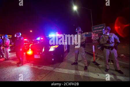 California Highway Patrol officers stand guard at an entrance of the 101 freeway in Los Angeles, California, following Monday's grand jury decision in the shooting of Michael Brown in Ferguson, Missouri, November 25, 2014. U.S. President Barack Obama said on Tuesday anyone who destroys property in rioting against a Missouri grand jury's decision should be prosecuted, urging Americans upset by the court to work together to improve race relations.  REUTERS/Mario Anzuoni  (UNITED STATES - Tags: CRIME LAW POLITICS CIVIL UNREST)