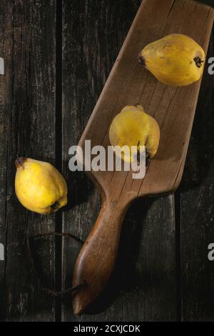 Three whole juicy quinces on old chopping board over wooden table in sunlight. Dark rustic style. Top view - Stock Photo