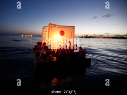 A lantern dedicated to victims of the earthquake and tsunami disaster that struck Japan floats on the water during the Na Lei Aloha Lantern Floating event held by the Shinnyo-en Buddhist at Ala Moana beach park on Memorial Day in Honolulu, Hawaii May 30, 2011.The event is held in honor of those killed by war, natural disasters and health reasons. REUTERS/Hugh Gentry (UNITED STATES - Tags: ANNIVERSARY SOCIETY) - Stock Photo