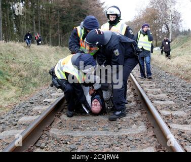 German police officers arrest anti-nuclear protester that remove stones from the railway tracks near Lemgrabe, November 26, 2011. The Castor (Cask for Storage and Transport Of Radioactive material) train is carrying 11 containers of spent German nuclear fuel on route from France after being reprocessed, to the nuclear waste storage facility of Gorleben in north eastern Germany this weekend. REUTERS/Fabrizio Bensch (GERMANY  - Tags: POLITICS CONFLICT ENVIRONMENT) - Stock Photo