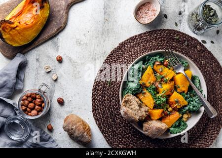Top view of season salad with grilled pumpkin, kale, chickpea, pepitas and nuts. Autumn vegetarian healthy recipe.