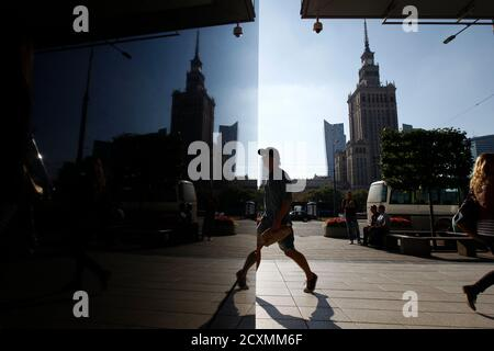 A man walks in Warsaw September 10, 2013. The Palace of Culture and Science is pictured in background. REUTERS/Kacper Pempel (POLAND - Tags: CITYSCAPE SOCIETY TRAVEL) - Stock Photo