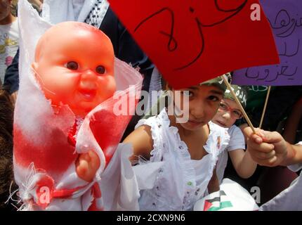 A girl, with her face painted with the Palestinian flag, carries a doll smeared with fake blood during a demonstration organised by Lebanese Sunni Islamists and Palestinians to denounce Israeli air strikes on the Gaza strip, in Lebanon's southern port-city of Sidon July 11, 2014. The United Nations human rights chief on Friday voiced serious doubts that Israeli's military operation against Gaza complied with international law banning the targeting of civilians, and called on both sides to step back from the brink. REUTERS/Ali Hashisho   (LEBANON - Tags: POLITICS CIVIL UNREST) - Stock Photo