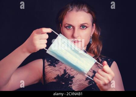 Vamp woman with medical mask, quarantine concept for halloween. Red-headed vampire woman holding a face mask