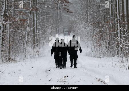 Police walk through a snow covered forest to where two anti-nuclear protesters of German environmental organisation Robin Wood lie chained to the tracks in Friedrichshagen between Greifswald and Lubmin December 16, 2010. A controversial shipment of four Castor containers with spent German nuclear fuel coming from Cadarache in France is expected to arrive at the interim storage of the north eastern German village of Lubmin on Thursday.   REUTERS/Christian Charisius (GERMANY - Tags: POLITICS ENVIRONMENT CIVIL UNREST) - Stock Photo
