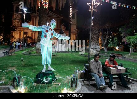 Men sit on a bench as a sidewalk mime artist performs at Colon Square in Cochabamba December 12, 2011. REUTERS/David Mercado (BOLIVIA - Tags: SOCIETY) - Stock Photo