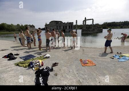 People get ready to swim near Murru prison, an abandoned Soviet prison, in Rummu quarry, Estonia, during hot weather July 4, 2015. During the Soviet time, Rummu quarry was used as a mining site for Vasalemma marble and most of the workforce came from among the detainees of Murru prison. When the prison closed after 1991, pumps that once kept the quarry and the prison dry were shut down, causing water to fill the quarry. It has become an unofficial and unguarded swimming and diving spot, attracting locals and tourists. REUTERS/Ints Kalnins - Stock Photo