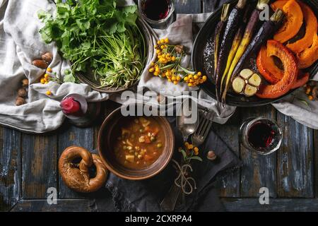 Holiday table decoration setting with bowls of hot soup, baking pumpkin, carrot, garlic, fresh coriander, pretzels bread, red wine, berries and candle - Stock Photo