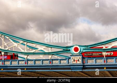 London, United Kingdom - September 14, 2017: Classic red London buses crossing the vibrant and colorful fragment of the famous Tower Bridge in London. - Stock Photo