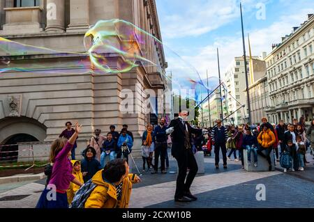 London, United Kingdom - September 16, 2017: Street artist dressed like British gentleman in black costume with hat cylinder performing for the kids b - Stock Photo