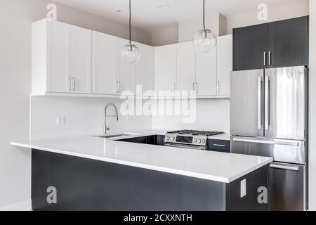 A black and white two toned kitchen with lights hanging above the marble counter top, stainless steel appliances, and white subway tile. - Stock Photo
