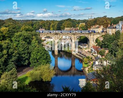 Passenger train crossing the Victorian railway viaduct across the River Nidd in early autumn Knaresborough North Yorkshire England