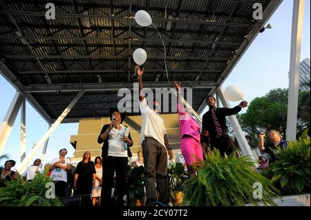 Parents of slain Florida teenager Trayvon Martin, Tracy Martin (2nd L) and Sybrina Fulton (2nd R), and Trayvon's older brother Javaris Fulton (R) are joined by Congresswoman Frederica Wilson (D-FL) as they release balloons into the air in memory of Trayvon towards the end of a rally protesting his shooting in Miami, Florida April 1, 2012. Thousands of protesters gathered in a downtown bayfront park on Sunday demanding the arrest of the neighborhood watch volunteer who shot and killed an unarmed black teenager, Trayvon Martin, in central Florida a month ago. REUTERS/Brian Blanco  (UNITED STATES