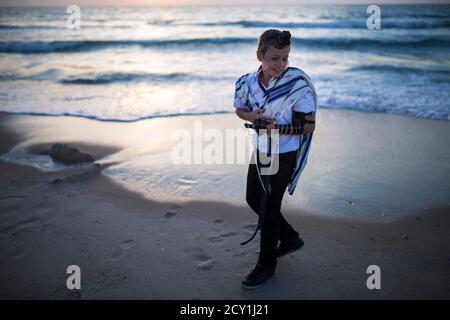 A Jewish boy wearing a prayer shawl and Tefillin, leather straps and boxes containing sacred parchments, has his Bar Mitzvah photographs taken on the shores of the Mediterranean Sea at Nitzanim beach, near the Israeli southern city of Ashkelon April 22, 2014.REUTERS/Amir Cohen (ISRAEL - Tags: SOCIETY RELIGION TPX IMAGES OF THE DAY)