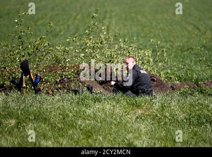 A Ukrainian soldier eats his meal in a field at a check point near Slaviansk, in eastern Ukraine April 27, 2014. The de facto mayor of the Ukrainian city of Slaviansk said on Sunday mediators from the Organisation for Security and Cooperation in Europe who are seeking the release of a group of detained observers had arrived in the city.  REUTERS/Marko Djurica (UKRAINE - Tags: POLITICS CIVIL UNREST MILITARY) - Stock Photo