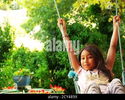 Young smiling mixed-race girl swinging in a park during the vacations - Stock Photo