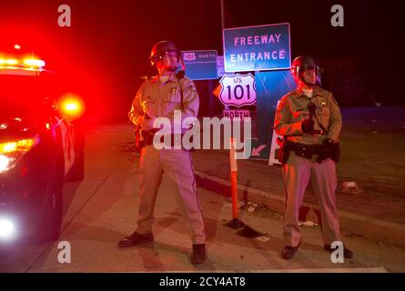 California Highway Patrol officers stand guard at an entrance of the 101 freeway in Los Angeles, California, following Monday's grand jury decision in the shooting of Michael Brown in Ferguson, Missouri, November 25, 2014.  U.S. President Barack Obama said on Tuesday anyone who destroys property in rioting against a Missouri grand jury's decision should be prosecuted, urging Americans upset by the court to work together to improve race relations.  REUTERS/Mario Anzuoni  (UNITED STATES - Tags: CRIME LAW CIVIL UNREST POLITICS)