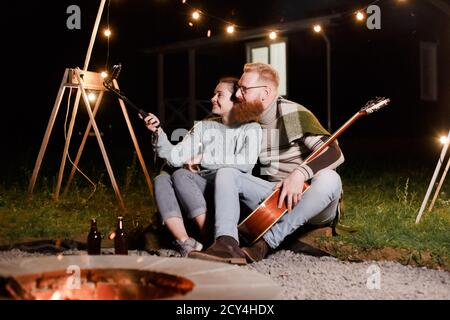 Happy caucasian couple, brunette woman and bearded man with guitar at picnic in countryside. Funny couple making selfie, smiling and have fun together