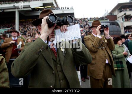 Racegoers watch the racing through binoculars during the Cheltenham Festival horse racing meet in Gloucestershire, western England March 16, 2011.   REUTERS/Eddie Keogh   (BRITAIN - Tags: SPORT HORSE RACING) - Stock Photo