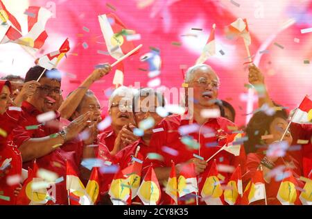 Malaysia's Prime Minister Najib Razak (2nd R) and other party leaders of the country's ruling United Malays National Organization (UMNO) wave UMNO's flags as they sing patriotic songs during its 66th anniversary celebrations in Kuala Lumpur May 11, 2012. REUTERS/Bazuki Muhammad (MALAYSIA - Tags: POLITICS ELECTIONS) Stock Photo