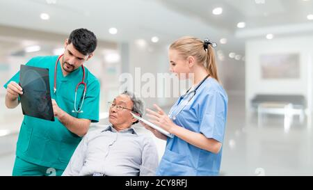 Surgeon showing xray film to senior patient looking at brain injuries with nurse standing beside the surgeon at the hospital room. Medical healthcare - Stock Photo