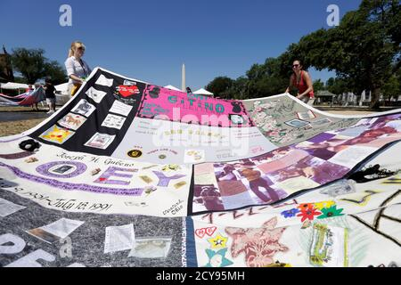 Volunteers unfold a quilt panel to mark the 25th anniversary of The AIDS Memorial Quilt and the 30 years since the HIV and AIDS epidemic was diagnosed in America, on the National Mall in Washington June 27, 2012.  The AIDS Memorial Quilt, is an enormous quilt made as a memorial to and celebration of the lives of people who have died of AIDS-related causes. The quilt is on display during the Smithsonian Folklife Festival which ends July 8. REUTERS/Kevin Lamarque  (UNITED STATES - Tags: HEALTH) - Stock Photo
