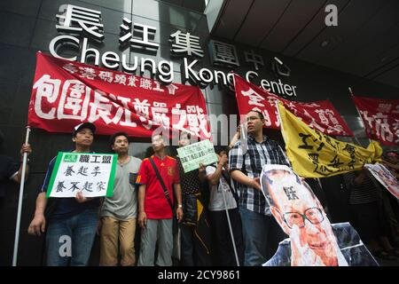 Dock workers march with a defaced picture of Hong Kong's tycoon Li Ka-shing during a strike outside Cheung Kong Center in Hong Kong's financial Central District April 17, 2013. Striking dock workers at a port operator backed by Hong Kong's richest man Li failed to reach a deal for higher pay, prolonging a dispute that could cost the city its position as the world's third-largest container port. REUTERS/Tyrone Siu (CHINA - Tags: BUSINESS EMPLOYMENT CIVIL UNREST) - Stock Photo
