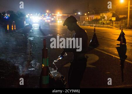A protester extinguishes a fire after tear gas was fired at demonstrators reacting to the shooting of Michael Brown in Ferguson, Missouri August 17, 2014. Shots were fired and police shouted through bullhorns for protesters to disperse, witnesses said, as chaos erupted Sunday night in Ferguson, Missouri, which has been racked by protests since the unarmed black teenager was shot by police last week. REUTERS/Lucas Jackson (UNITED STATES - Tags: CIVIL UNREST CRIME LAW) - Stock Photo